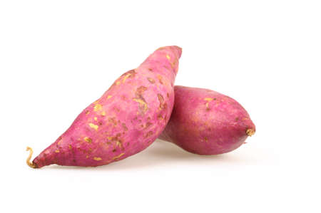 Whole purple yams photographed on a white background.