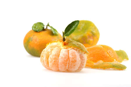 Naturally ripened peeled tangerine on a white background. Imagens