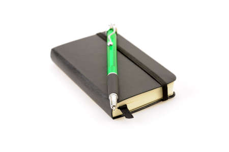 Little black note book and a pen photographed on a white background.