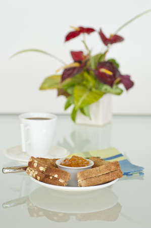 Breakfast consisting of toast with orange marmalade and coffee.