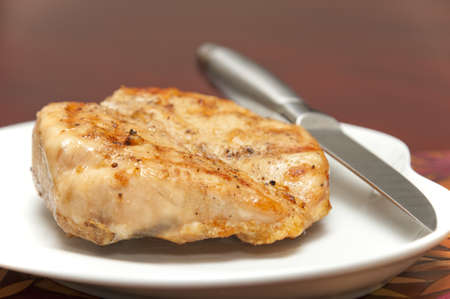 Grilled chicken breast with focus on the grill marks on top of the meat.