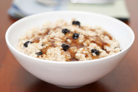 oatmeal: Bowl of oatmeal with raisins and maple syrup photographed closeup  Stock Photo
