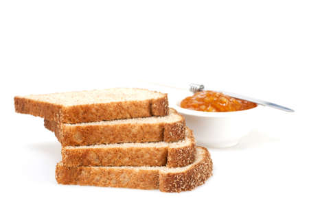 Several slices of whole grain bread with spread photographed on a white background. Stock fotó