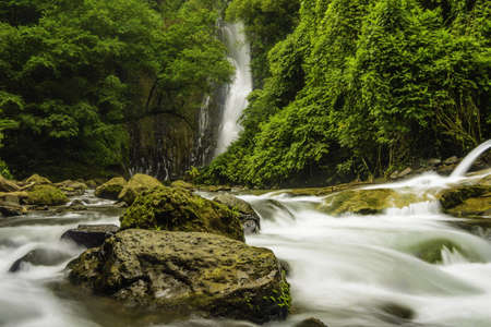 Fast flowing mountain stream in Costa Rica with a waterfall in the background. photo
