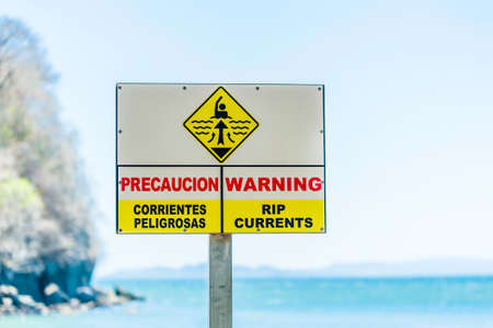 currents: Warning sign for rip currents near an ocean beach. Stock Photo