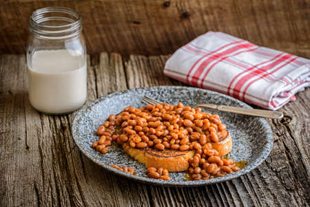 beans on toast: Plate of baked beans with toast on a rustic background. Stock Photo