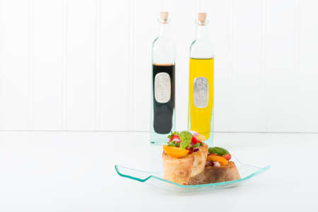 balsamic vinegar: Colorful bruschetta and bottles of olive oil and balsamic vinegar.  Suitable for many food service promotional applications. Stock Photo