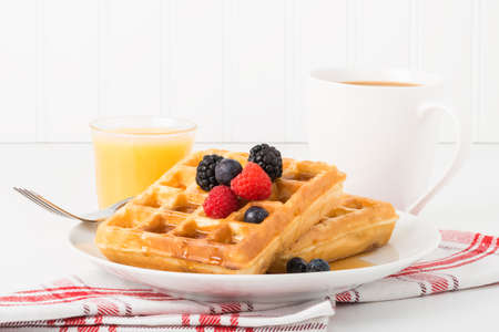 maple syrup: Stack of fresh waffles with maple syrup and fruit.