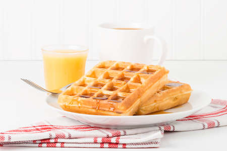 maple syrup: Fresh made waffles and maple syrup served with juice and coffee. Stock Photo