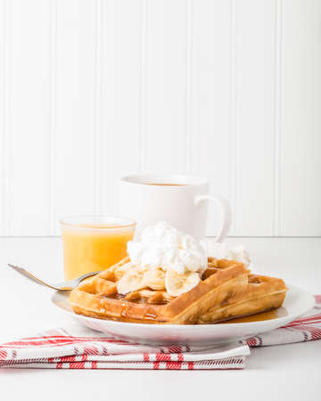 maple syrup: Delicious banana waffles with maple syrup and whipped cream.