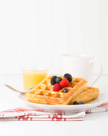 maple syrup: Plate of waffles with fresh fruit and maple syrup.