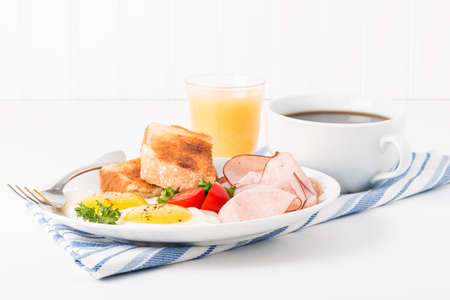 sunny side: Eggs sunny side up served with ham, coffee and toast. Stock Photo