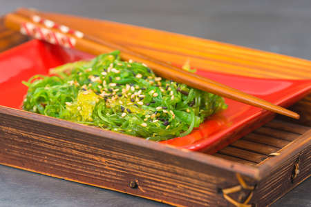 person appetizer: Fresh seaweed salad on a red plate in a bamboo server.