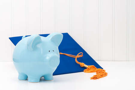 cost of education: Blue piggy bank and graduation cap.  Conveys the concept of the cost of higher education.