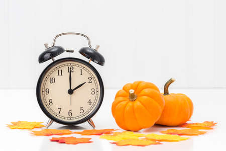 Alarm clock with colorful fall leaves and pumpkins to represent the concept of daylight savings time.