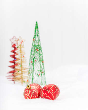 Two red glass Christmas decorations with colorful trees in the background.