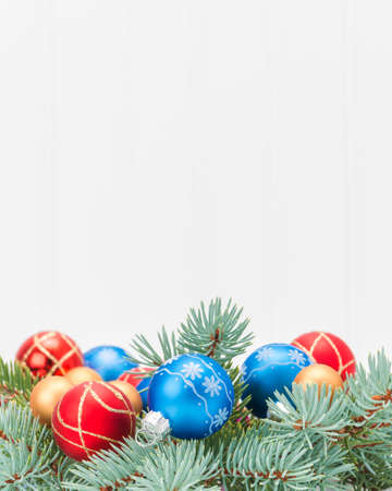 adorned: Spruce bough adorned with colorful glass christmas decorations.