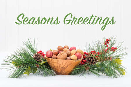 Wooden bowl of mixed nuts surrounded by a festive garland.
