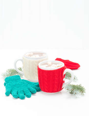Two mugs pf creamy hot chocolate with mittens and spruce branches. Stock Photo