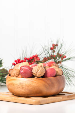 Bowl of whole mixed nuts with a seasonal background.