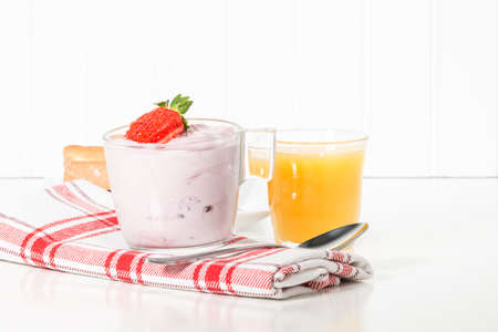 Cup of strawberry greek yogurt served with orange juice.