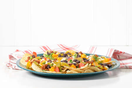 Delicious hot nachos on a green tin platter. Imagens
