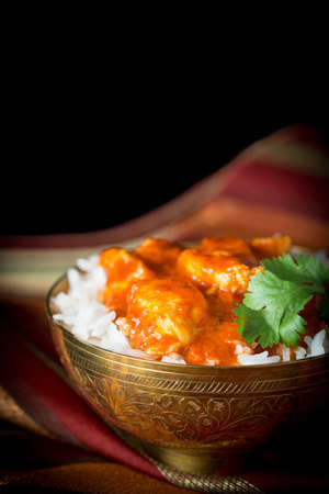 Indian butter chicken served on a bowl of basmati rice. Stock Photo