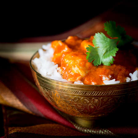 Bowl of spicy indian butter chicken in white basmati rice. Stock Photo