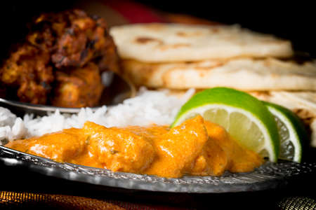 Closeup of dinner plate featuring chicken korma, rice, pakoras and nan bread.
