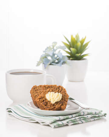 Fresh bran muffin and butter served with coffee. Imagens