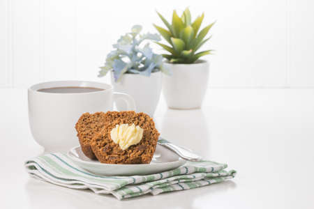 Fresh bran muffin with butter served with coffee.