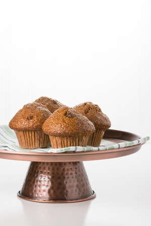 Raisin bran muffins on a copper presentation platter.