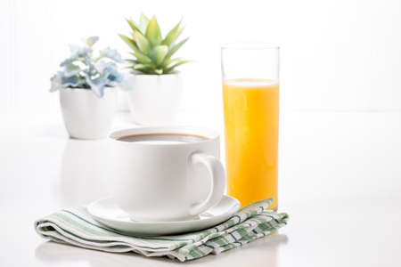 Cup of hot coffee and glass of orange juice with potted plants in background. Imagens