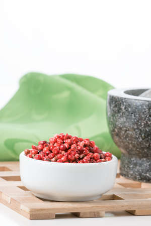 Bowl of pink whole peppercorns with a small part of a mortar and pestle in the background.
