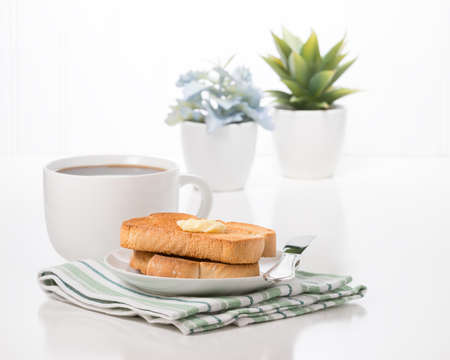 Toast with butter and a cup of hot coffee.
