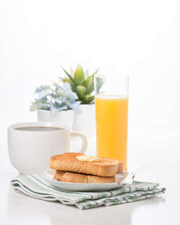 Breakfast consisting of toast with butter, coffee and orange juice.