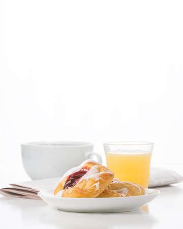 Verse framboos Deens en koffie met de ochtendkrant op de achtergrond.