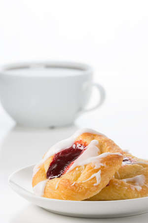Fresh raspberry danish with coffee in the background.