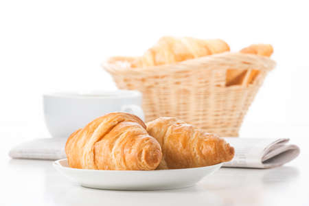 Fresh baked croissants served with coffee and a newspaper.