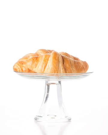 Fresh made buttery croissants on a glass stand.