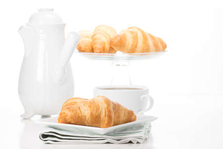 Fresh buttery croissants served with a cup of coffee. Imagens