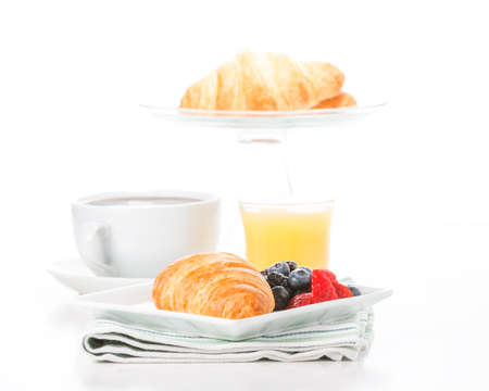 Fresh croissant and fruit served with coffee and orange juice. Imagens