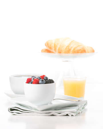 Small bowl of fresh berries served with croissant, coffee and orange juice.