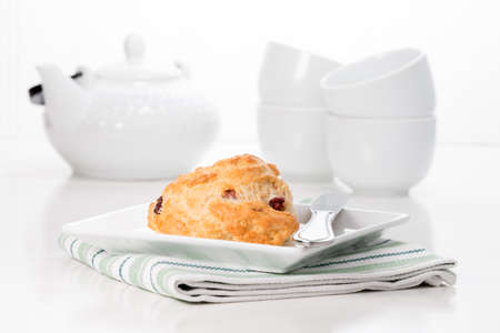 Fresh cranberry lemon scone served with coffee.