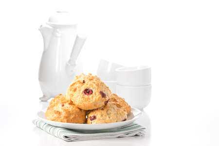 Fresh lemon cranberry scones with a coffee pot and cups in the background. Imagens