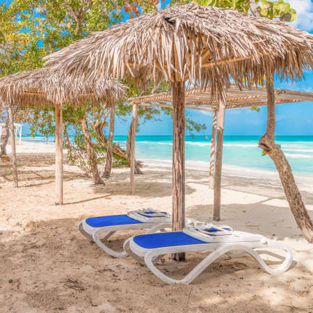 Two chairs await under a cabana at a quiet beach on the caribbean. Stock Photo