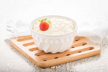 Bowl of creamy rice pudding garnished with a ripe whole strawberry. 免版税图像
