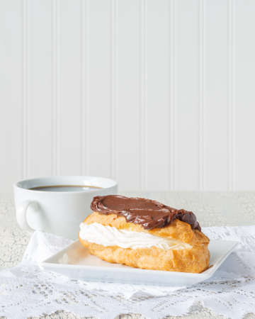 Delicious chocolate eclair served with fresh coffee.