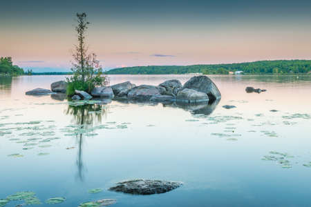 Granite rocks dot the still waters of Lower Buckhorn Lake at sunset.