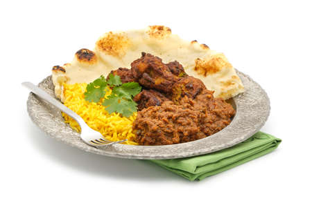 Plate of Indian food including beef vindaloo, rice, pakora and nan bread on a white background.